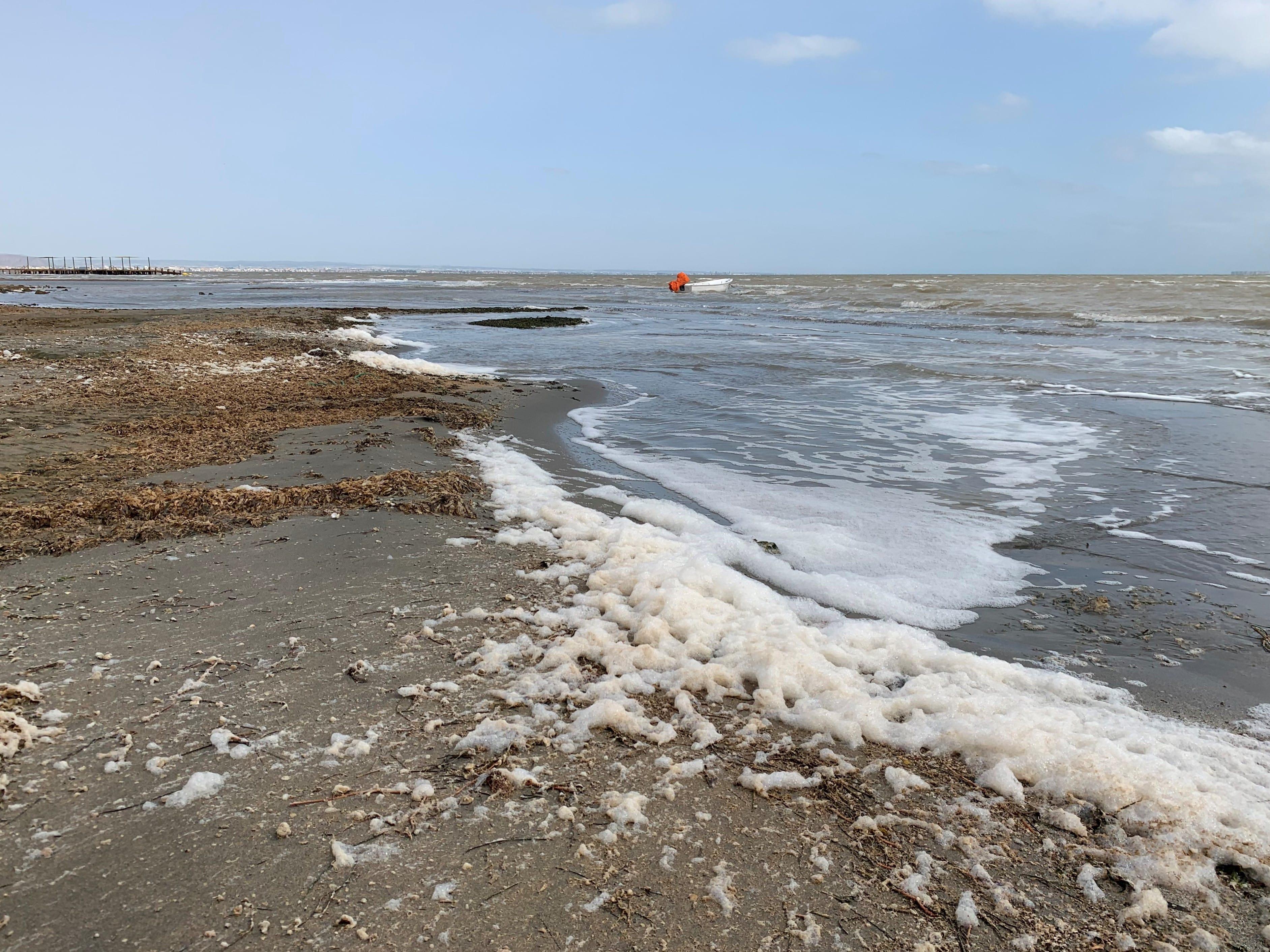 Espuma acumulada en la orilla de la playa de Los Urrutias